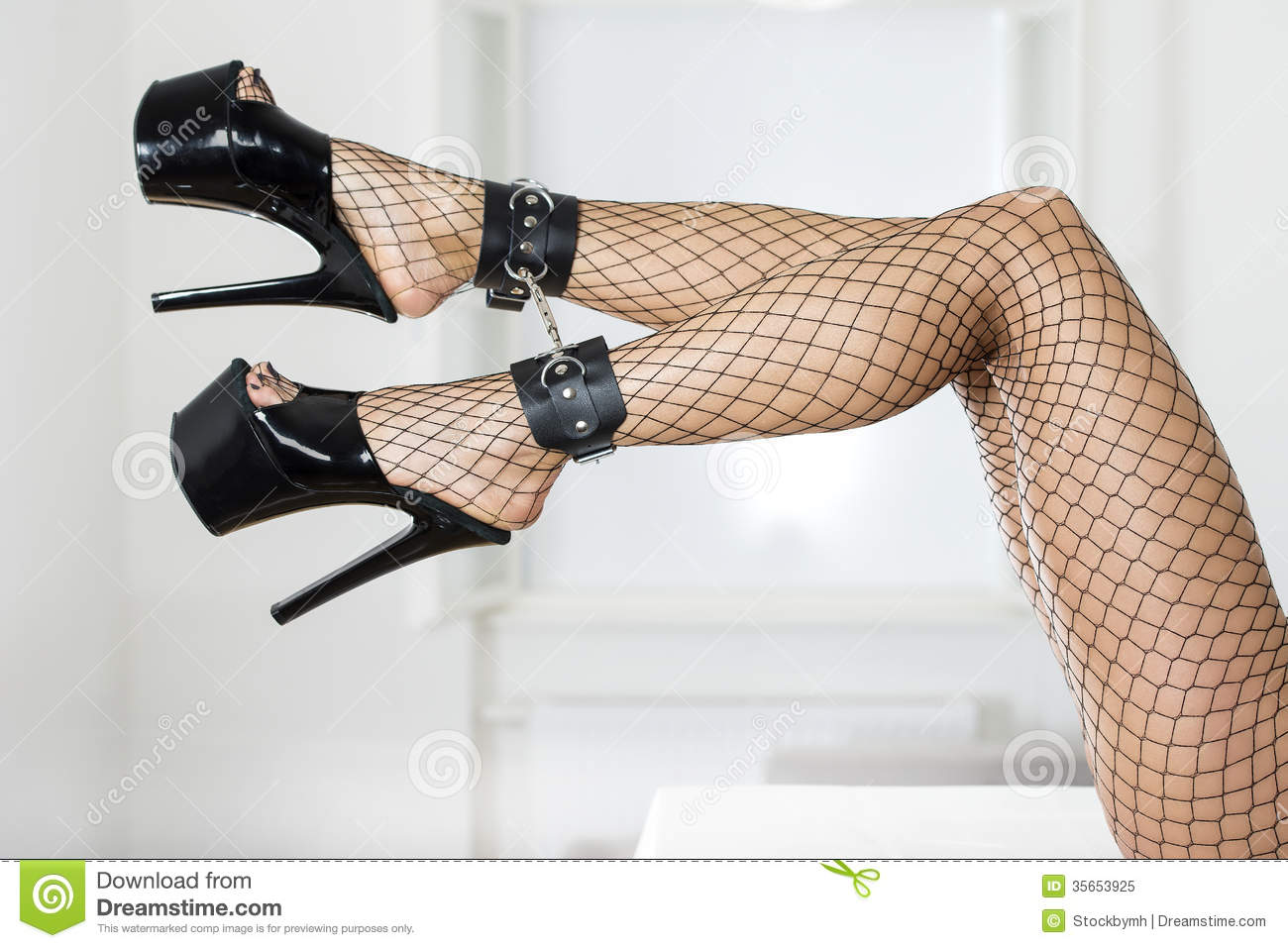 Long and sexy female legs with fishnet stockings, ankle cuffs and ...