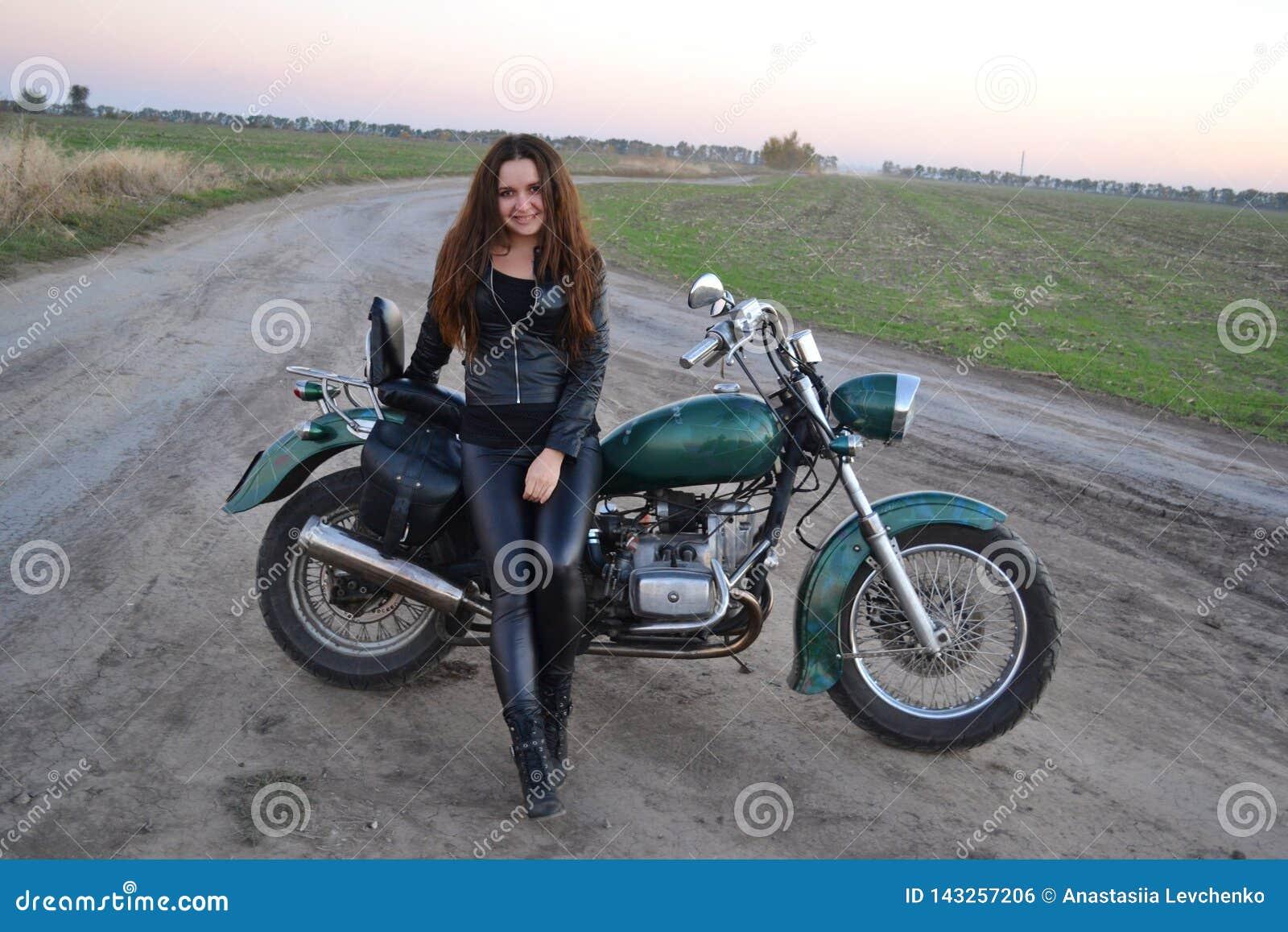Sexy Mädchen des Radfahrers, das auf kundenspezifischem Motorrad der Weinlese sitzt Lebensstil im Freien tonte Porträt