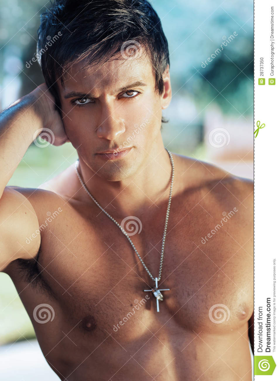 Close-up portrait of handsome shirtless man outdoors.