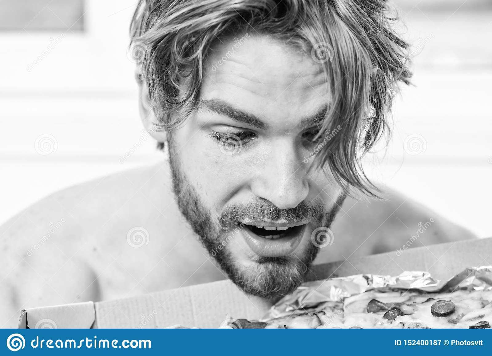 man eat pizza lying on bed. Student is at home on the bed in a bright apartment eating a tasty pizza. Man bearded