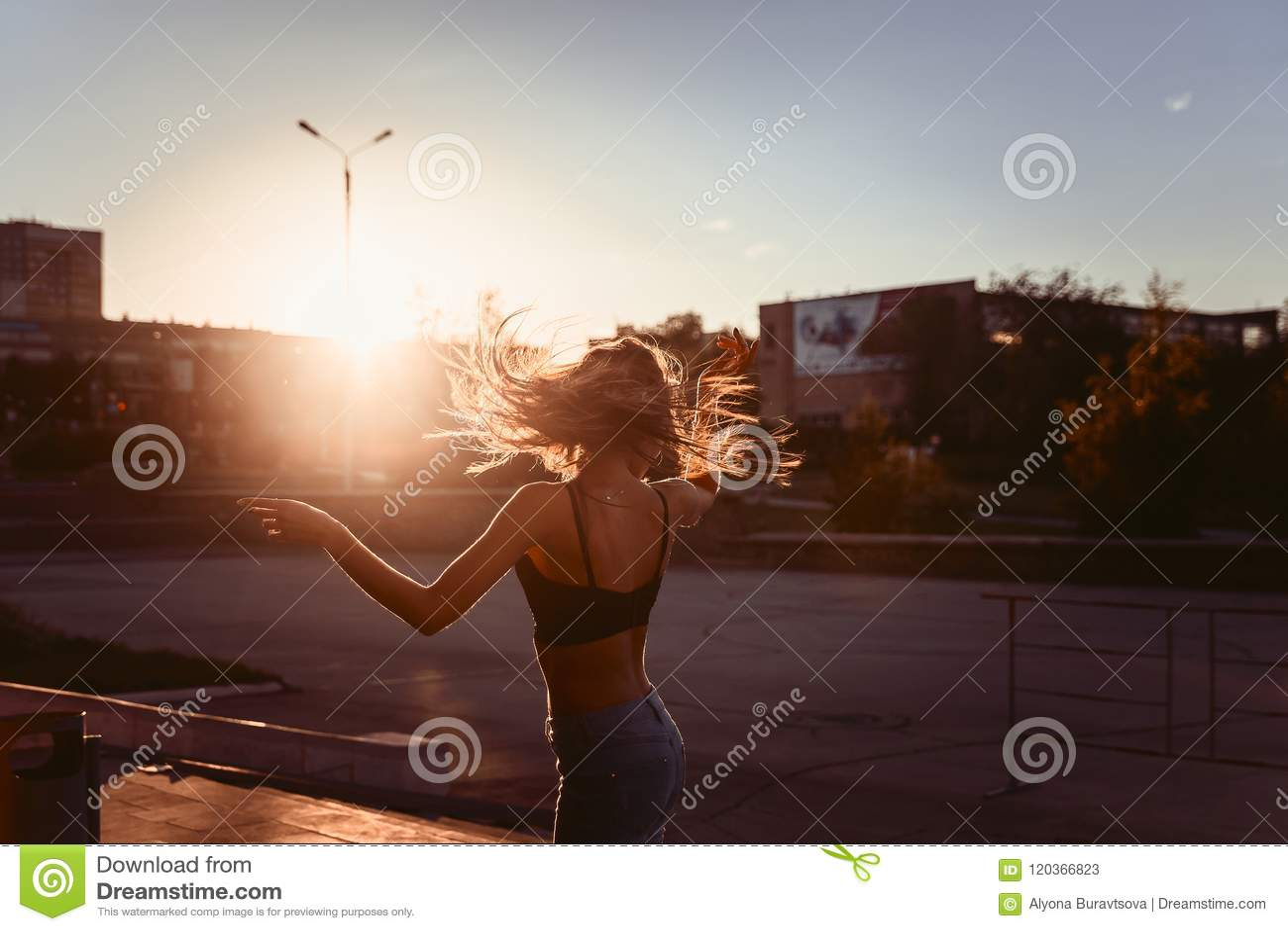Sexy meisje die in de stad bij zonsondergang dansen