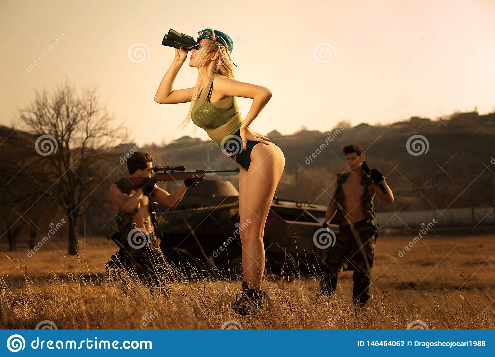 Sexy military girl with binoculars searching something ,on the highlands background with strong armed soldiers.