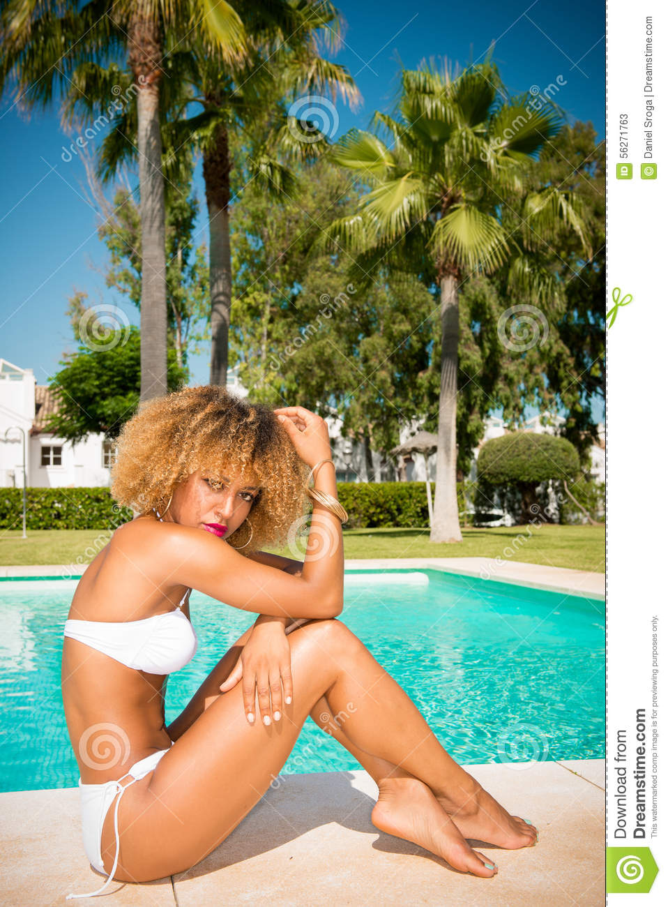 48eebe579d2 Model with Afro Haircut Posing Next to Exotic Swimming Pool She Wearing  White Skimpy Bikini