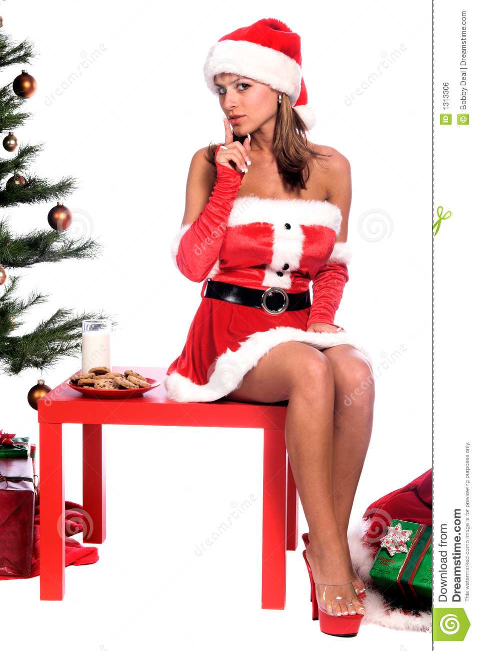 Sexy Ms. Santa Claus sitting by the Christmas tree with milk and ...