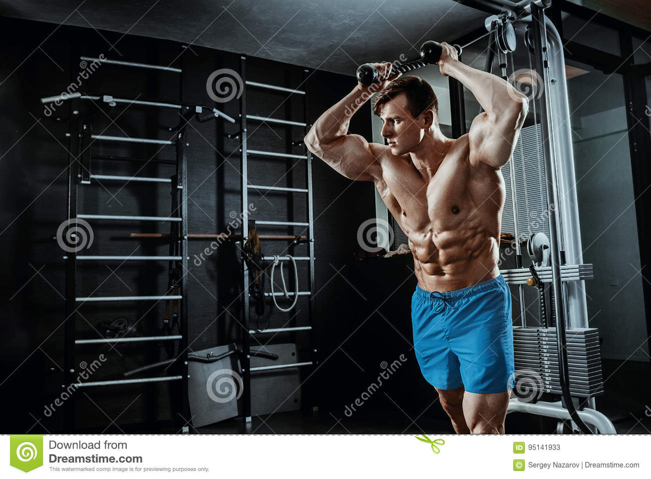 muscular man posing in gym, shaped abdominal. Strong male naked torso abs, working out