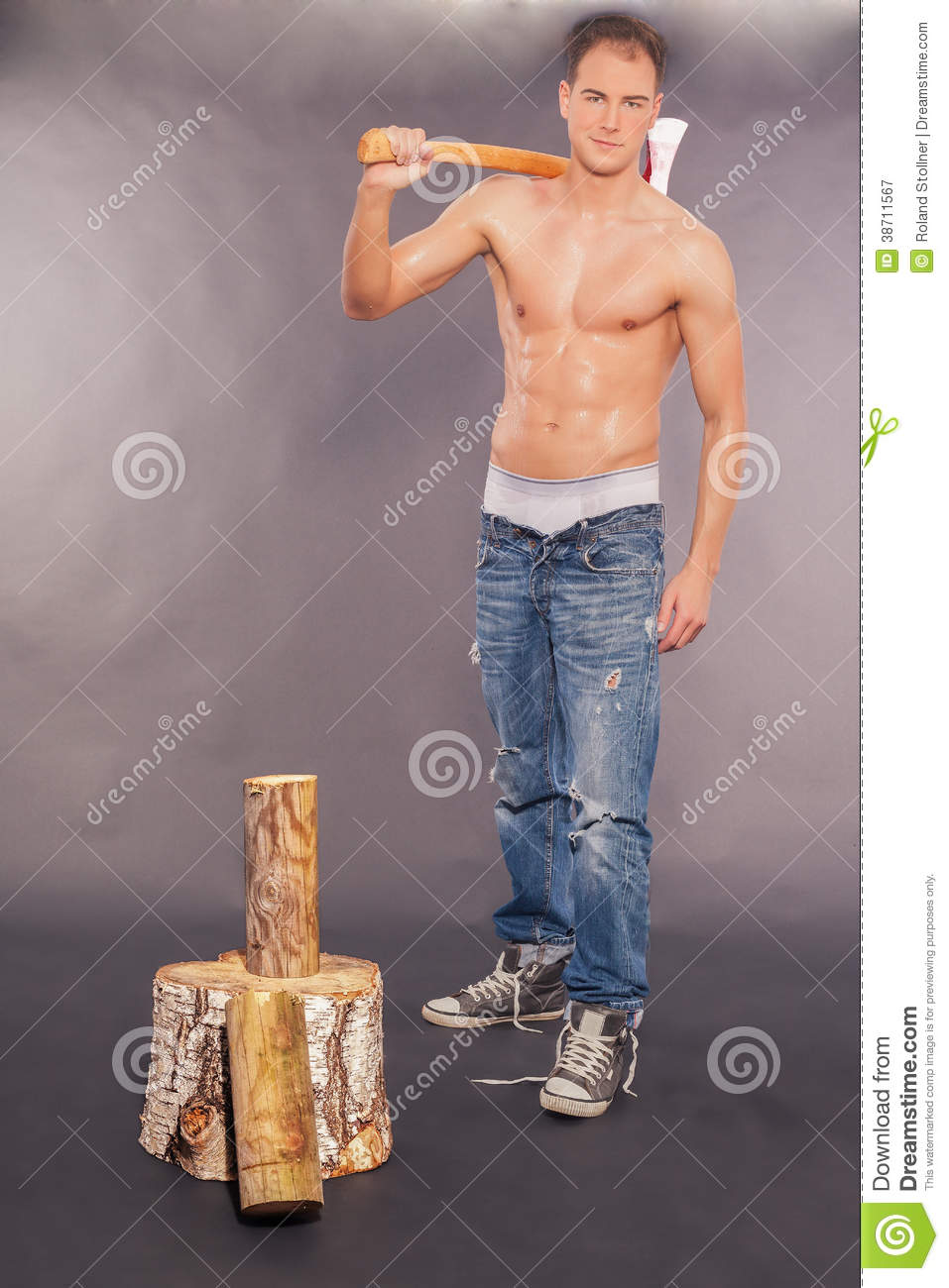 aa7500dd05c handsome muscular young man standing shirtless in jeans and sneakers  holding an axe chopping fire wood on a graduated grey studio background