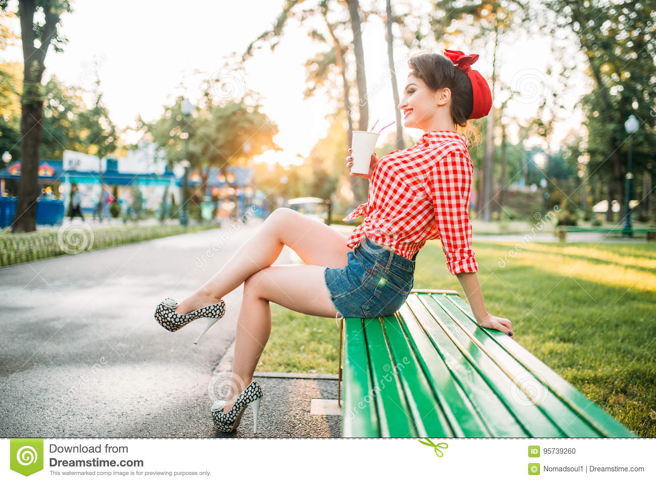 pinup girl holds cardboard cup with a straw
