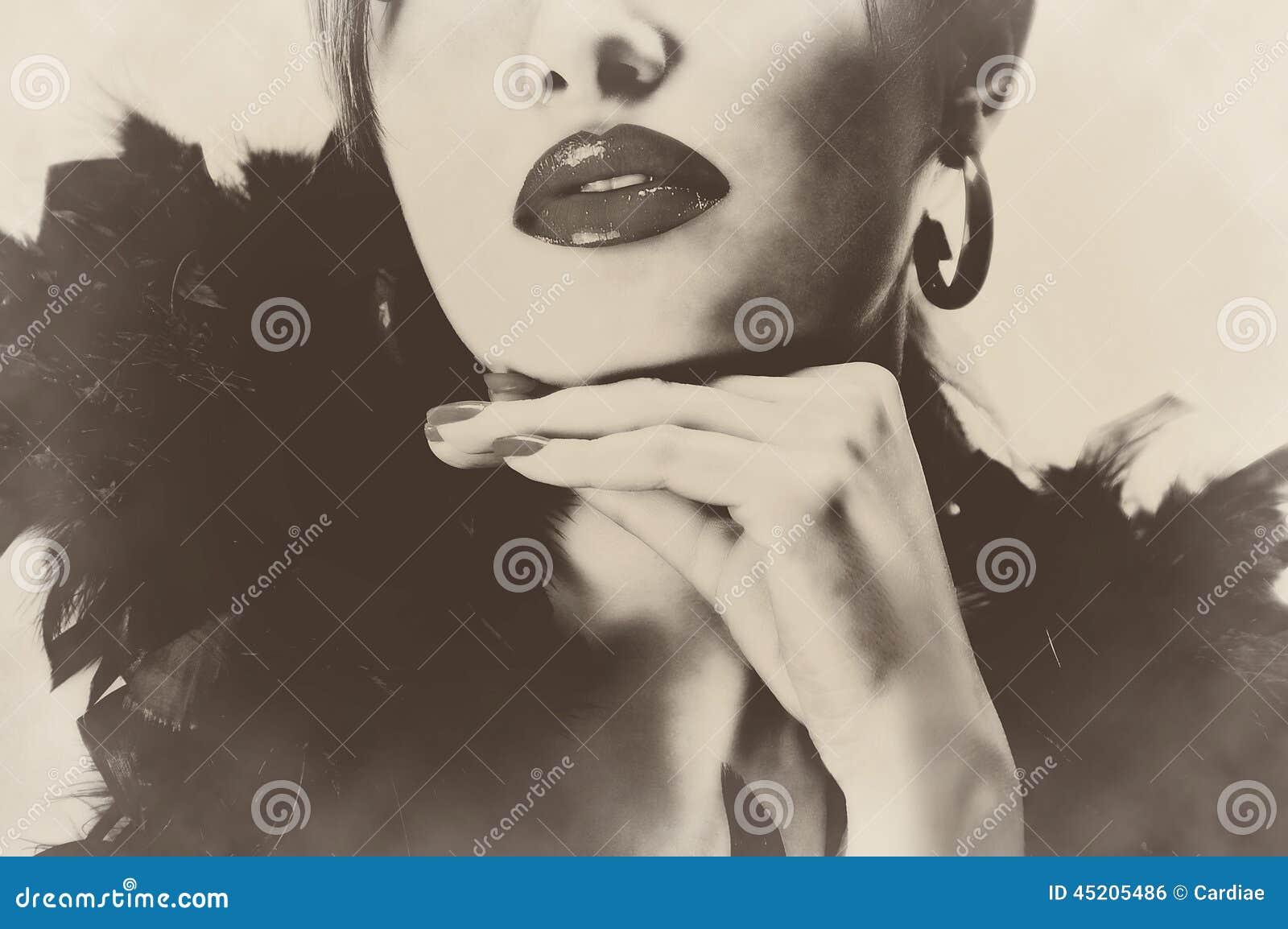 pretty beautiful woman with black feathers, shiny lips sepia retro vintage