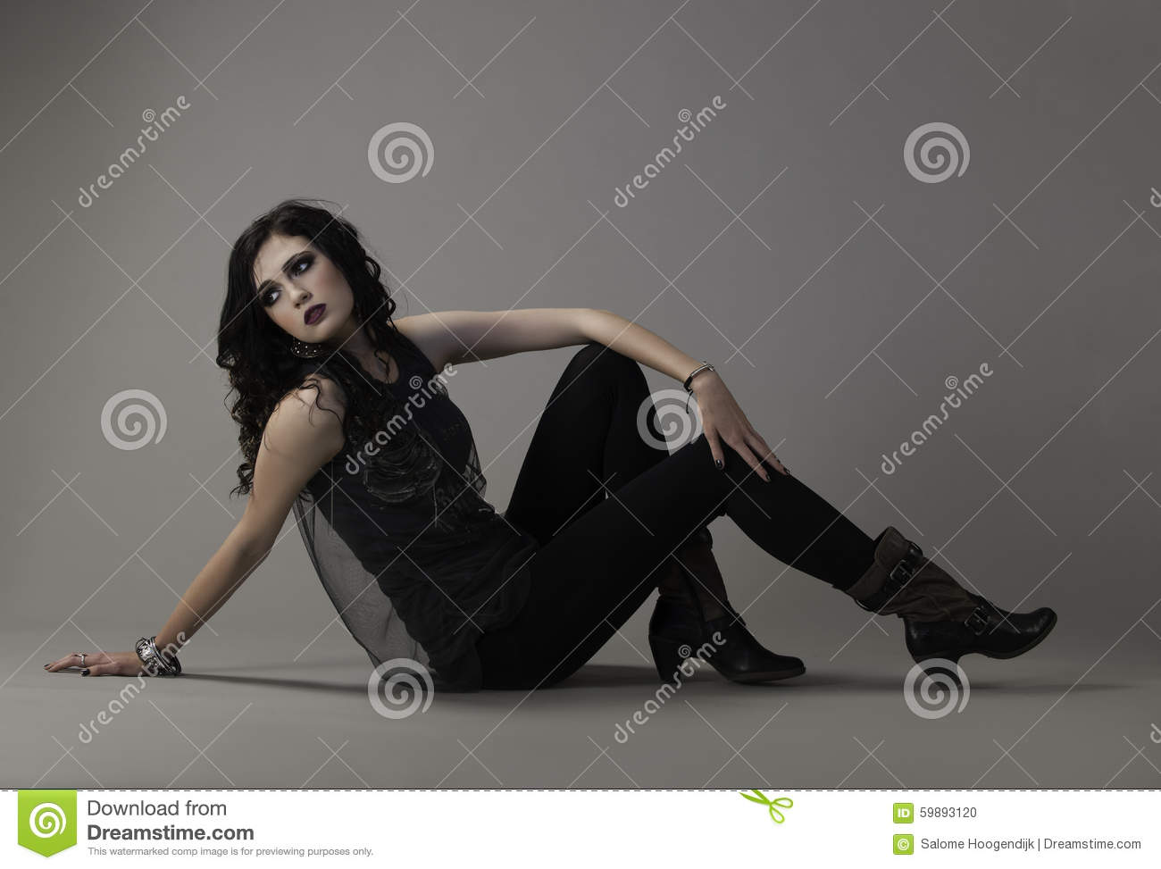 Portrait in color of a beautiful dark haired woman, wearing dramatic dark makeup with edgy clothing and boots, seated on the ground while looking back over ...