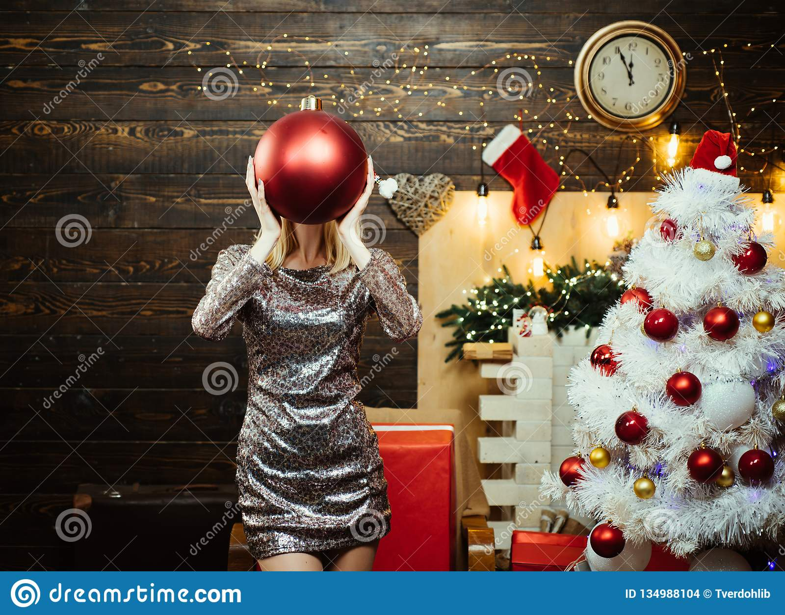 Santa woman posing on vintage Christmas background. Christmas tree decorate at home. Beautiful smiling woman wishes