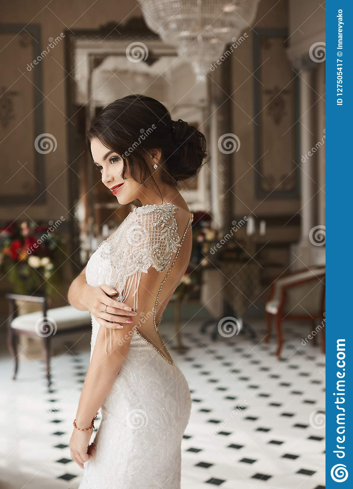 and sensual brunette model girl with bright make-up and fashionable hairstyle, in a stylish lace dress with naked