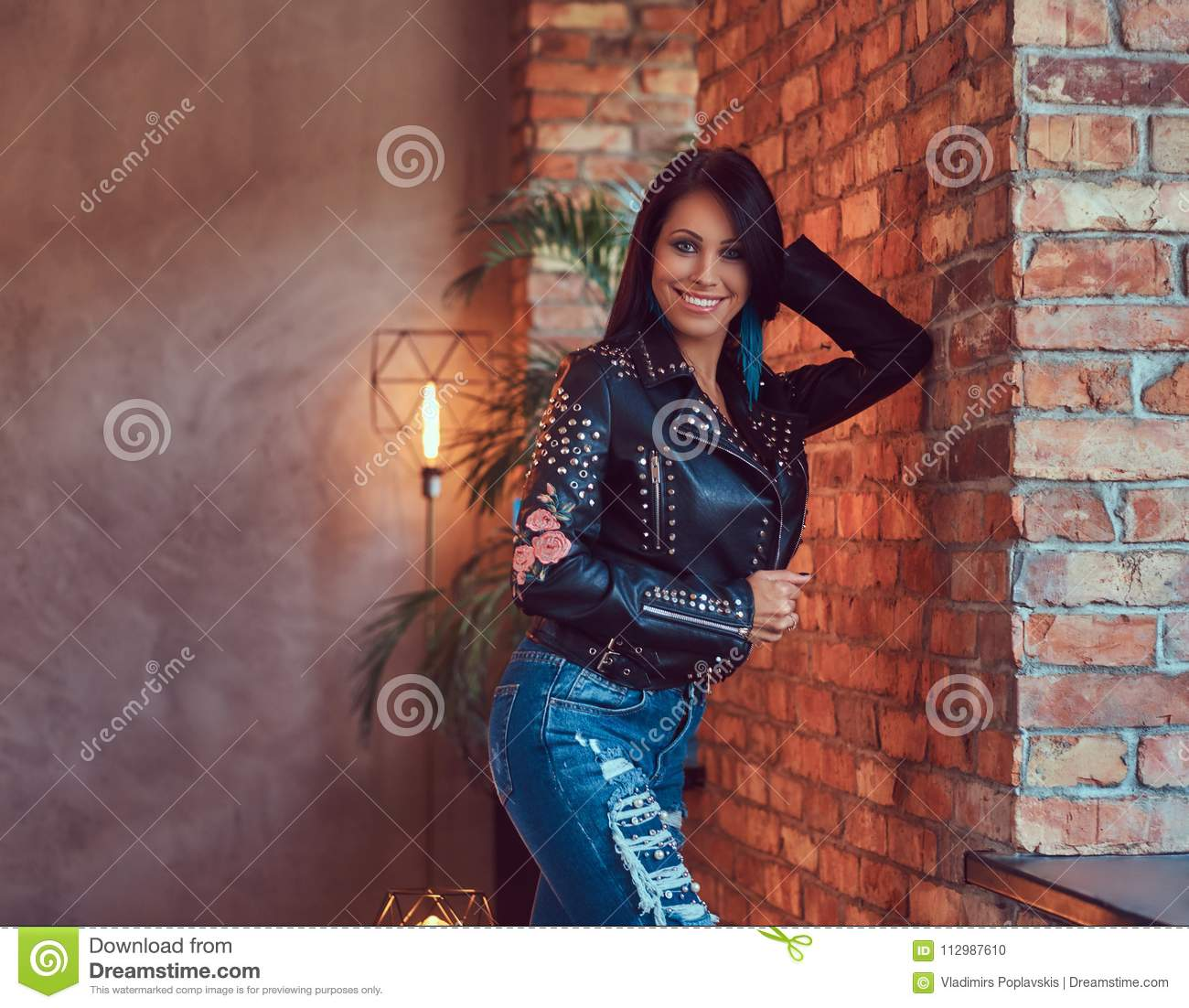 sensual brunette posing in stylish leather jacket and jeans leaning against a brick wall.