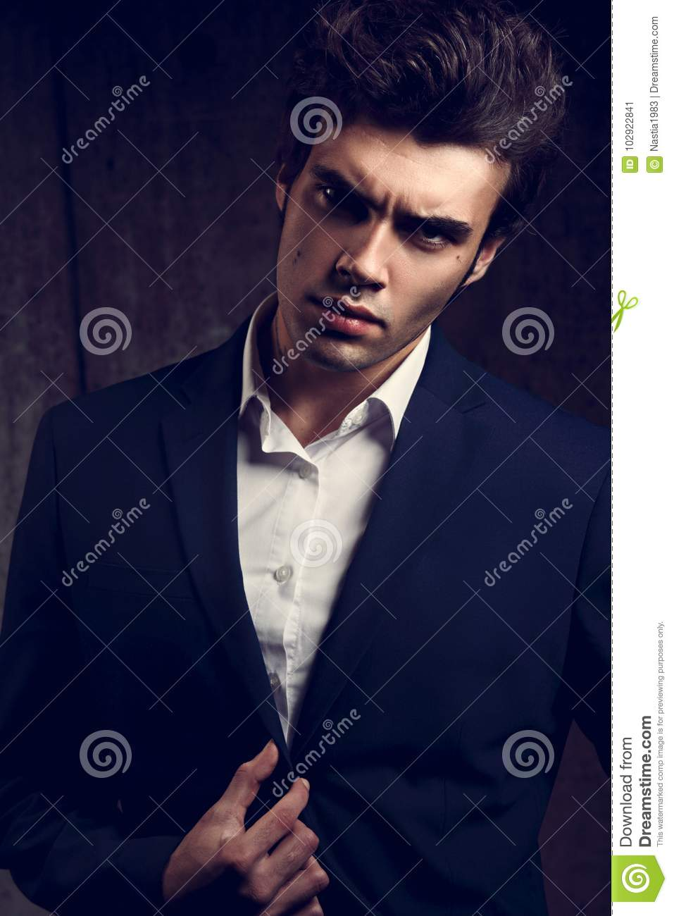 dfb210f2 serious handsome male model posing in blue fashion suit and white style  shirt on dark shadow background. Closeup fashion portrait. Toned color