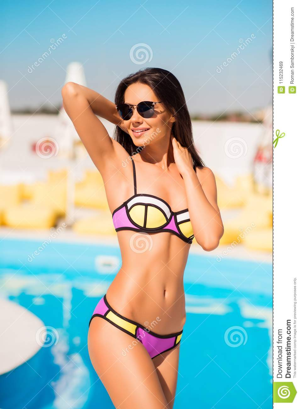 e63f1763604d6 slim brunette gorgeous girl in sun glasses is standing by the swimming pool  in colorful swim suit, so hot and attractive, figure is ideal, ...
