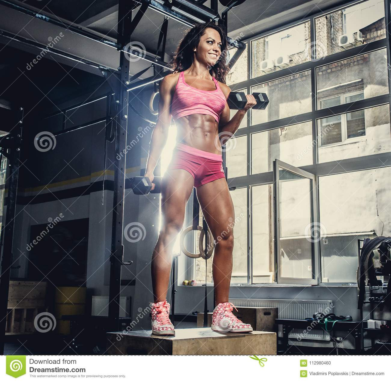 sporty female in pink sportswear holding barbell.