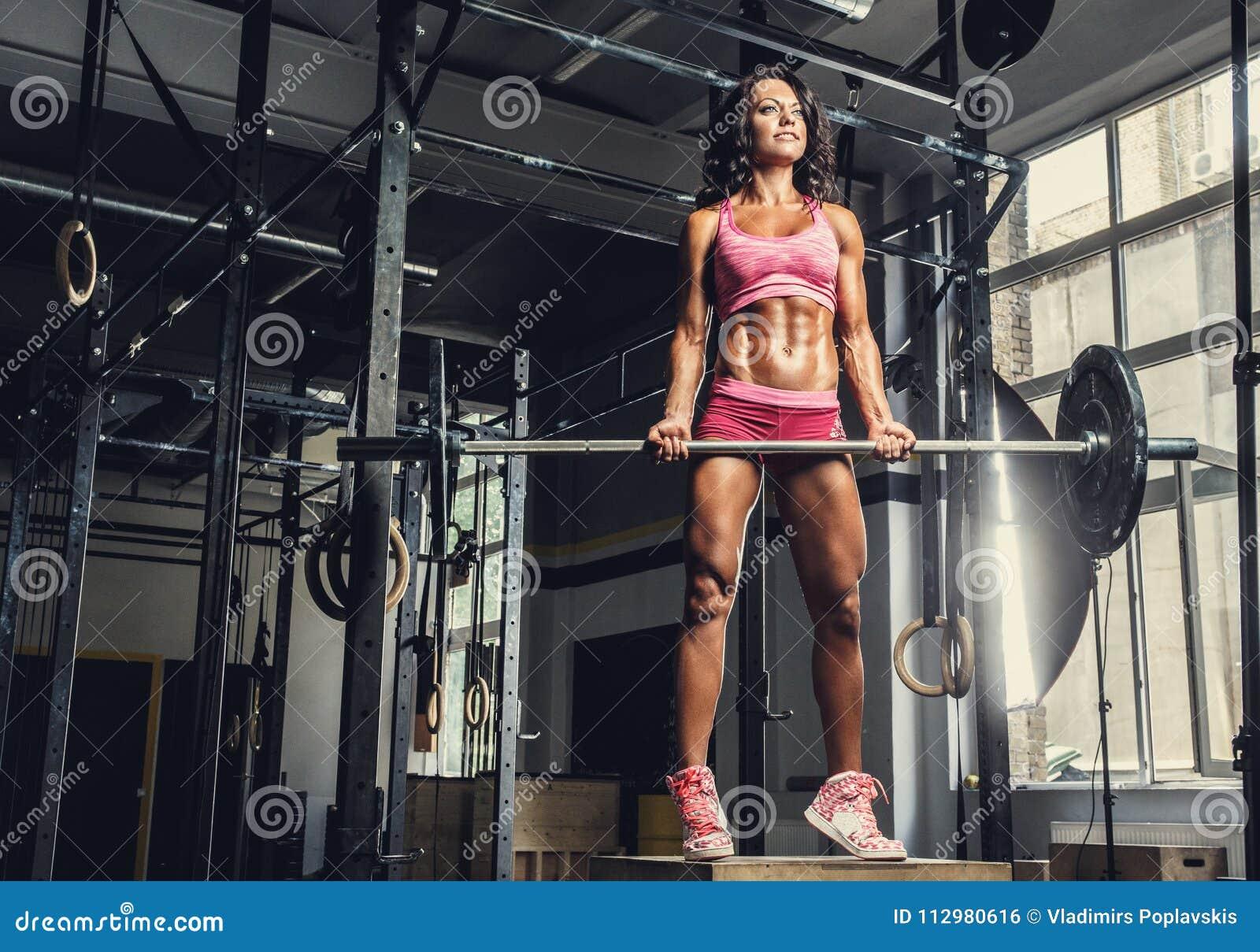 sporty female in pink sportswear holding barbell.