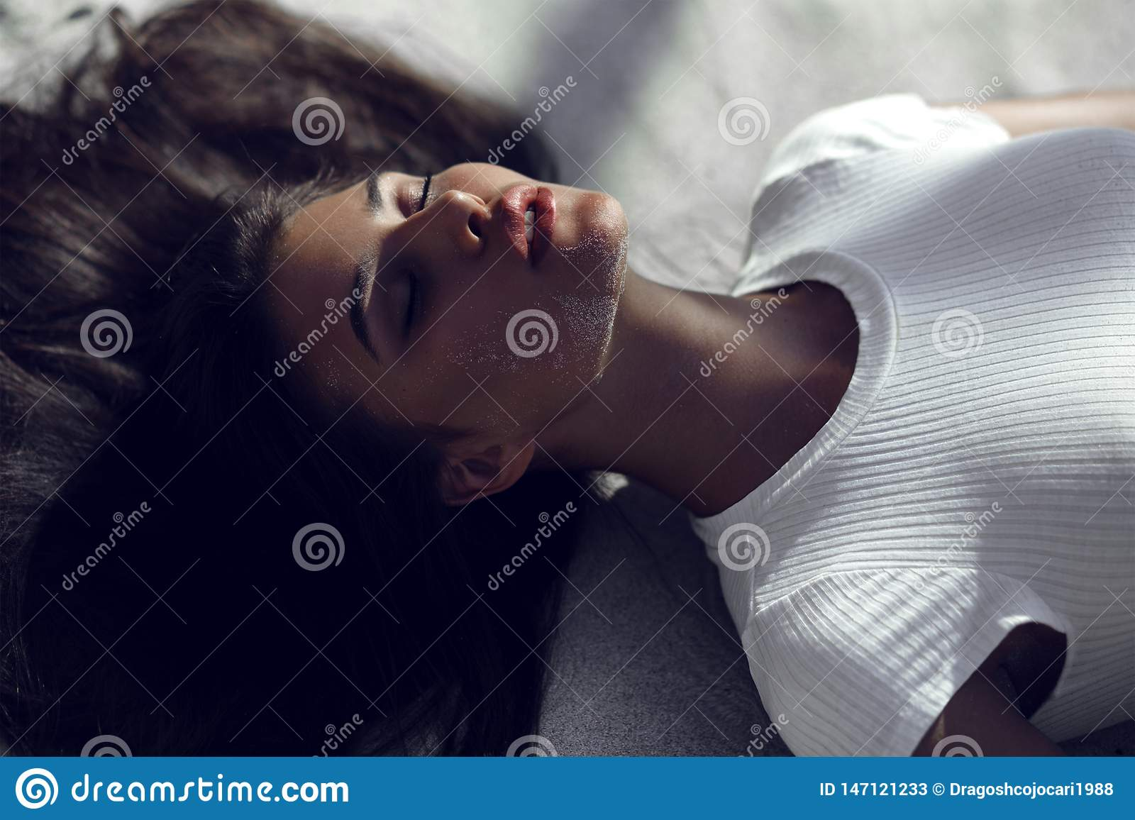 tanned brunette girl with closed eyes and big sensual lips, lying on beach on white sand with shadows on the face.