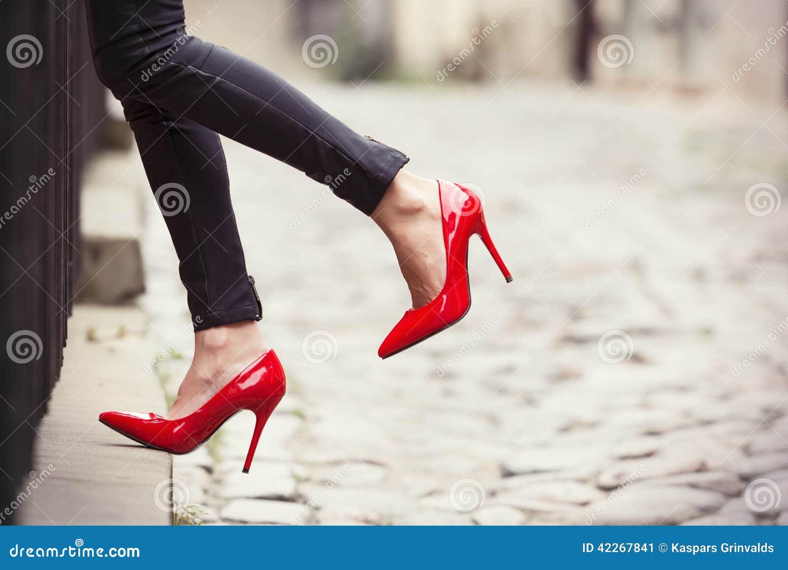 Sexy vrouw die rode hoge hielschoenen in stad dragen