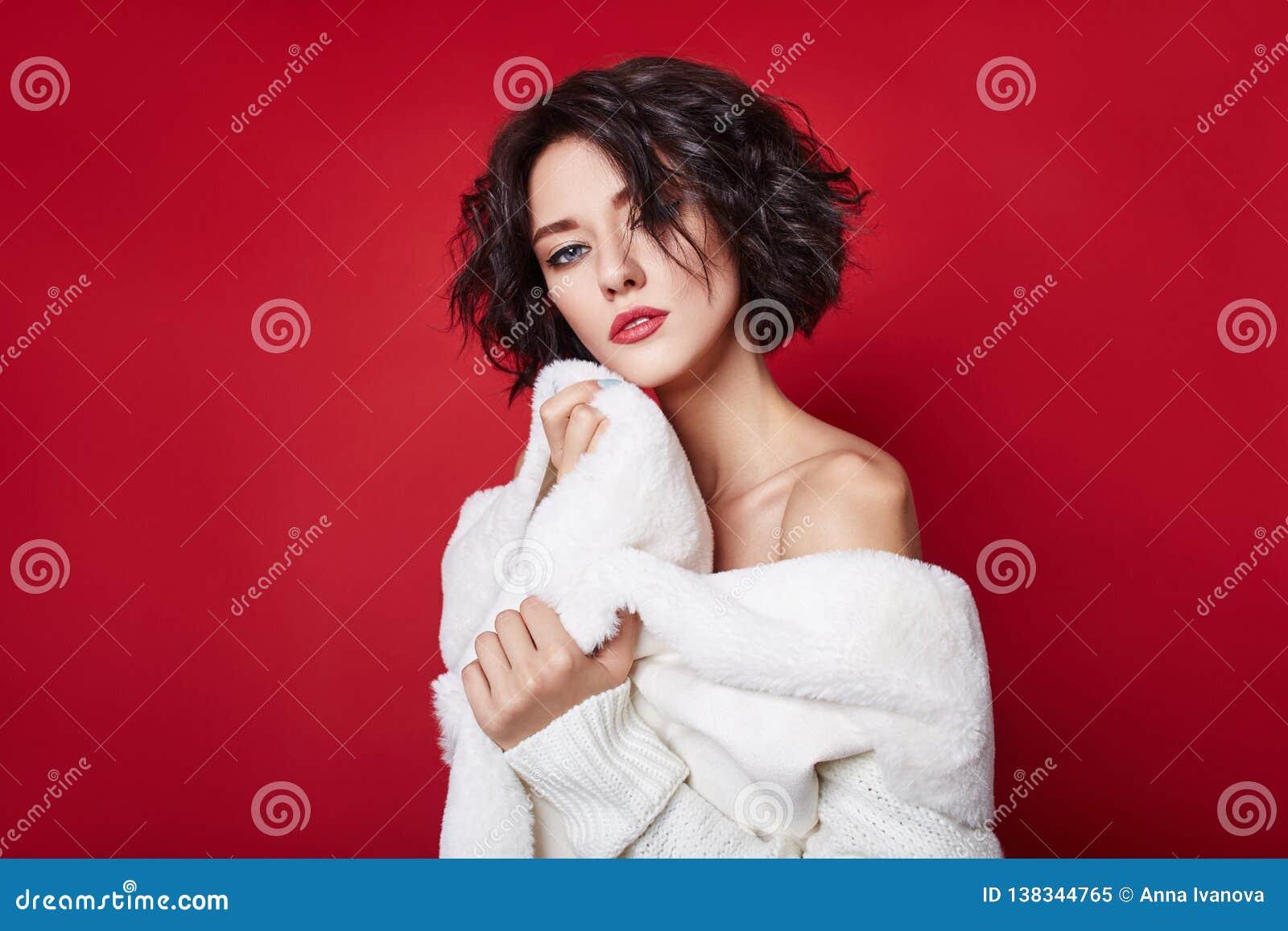 Sexy vrouw met kort die haar in witte sweater op rode achtergrond wordt gesneden Perfect meisje met nat slonzig donker haar en he