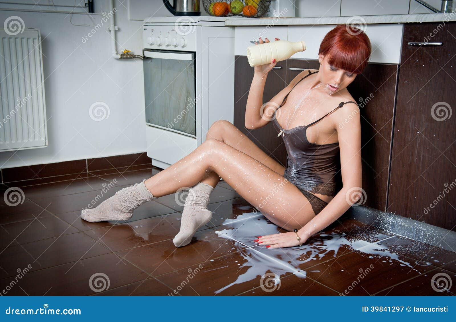 Sexy vrouw in overhemd en sokken die melk morsen van een fles