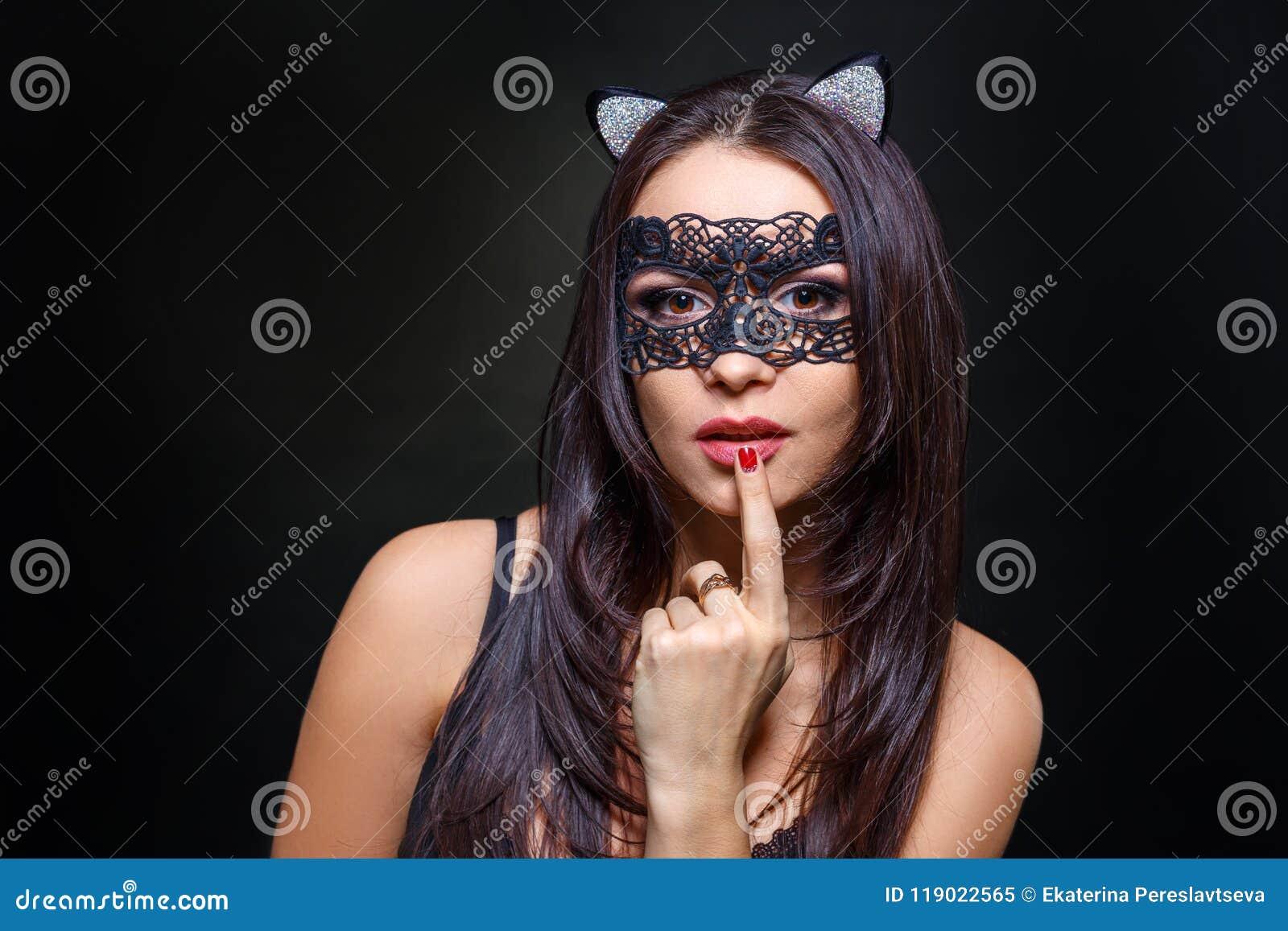 Sexy vrouw in zwarte lingerie en masker op zwarte achtergrond