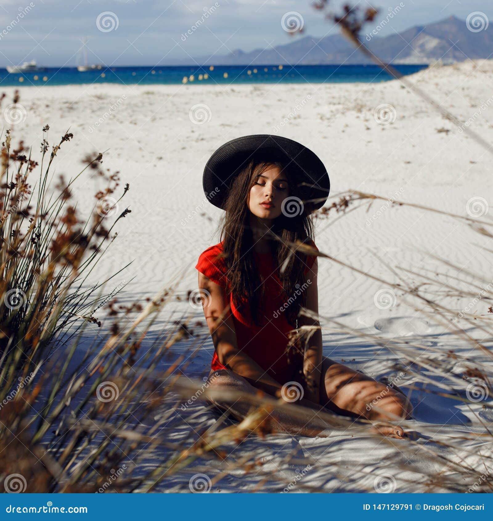 Sexy weibliches Modell, das auf dem Strand auf Sand im roten Badeanzug mit schwarzem Hut, mit geschlossenen Augen, auf einem Meer