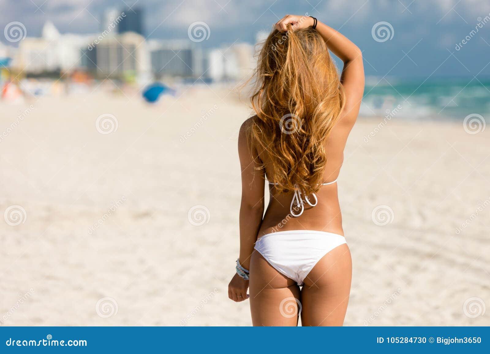 woman in a bikini on beach with back to camera