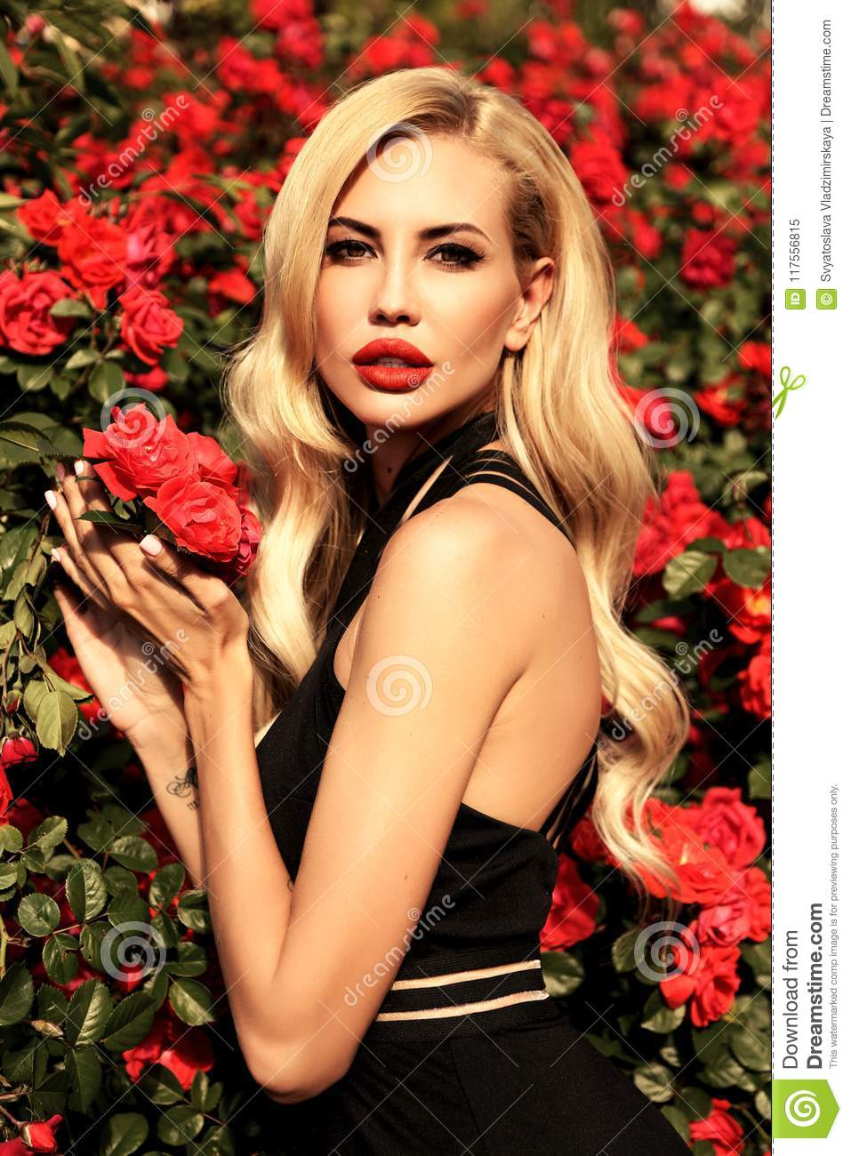 woman with blond hair in luxurious dress posing in spring g