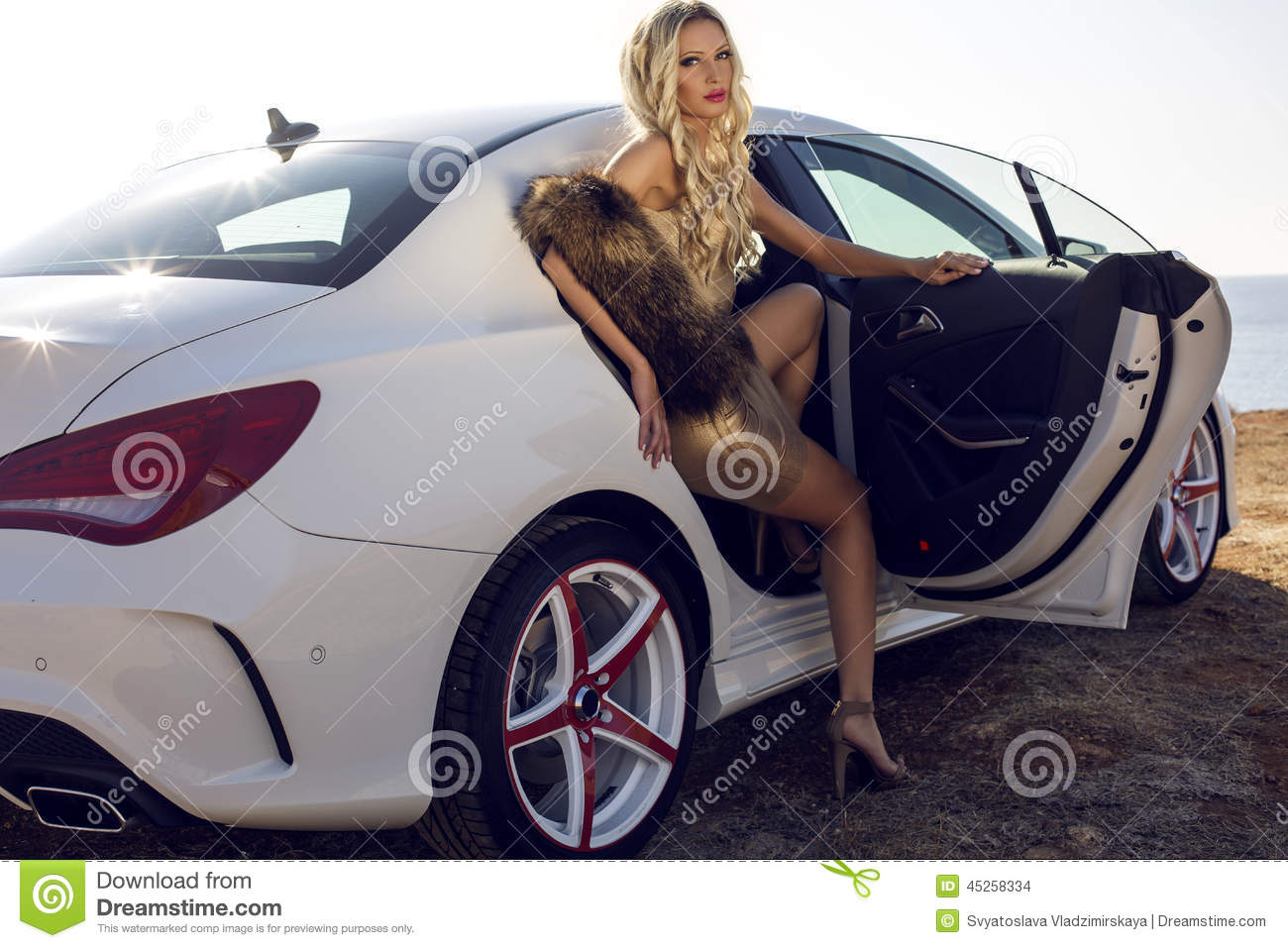 Woman with blond hair posing in luxurious white car stock for Interieur voiture de luxe