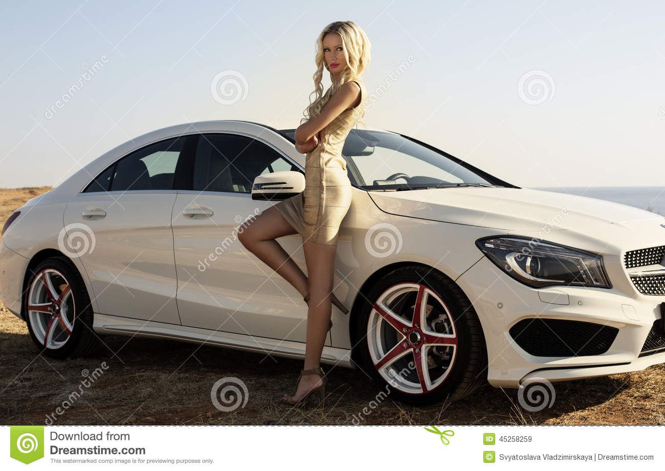 Woman With Blond Hair Posing Beside A Luxury Auto Stock
