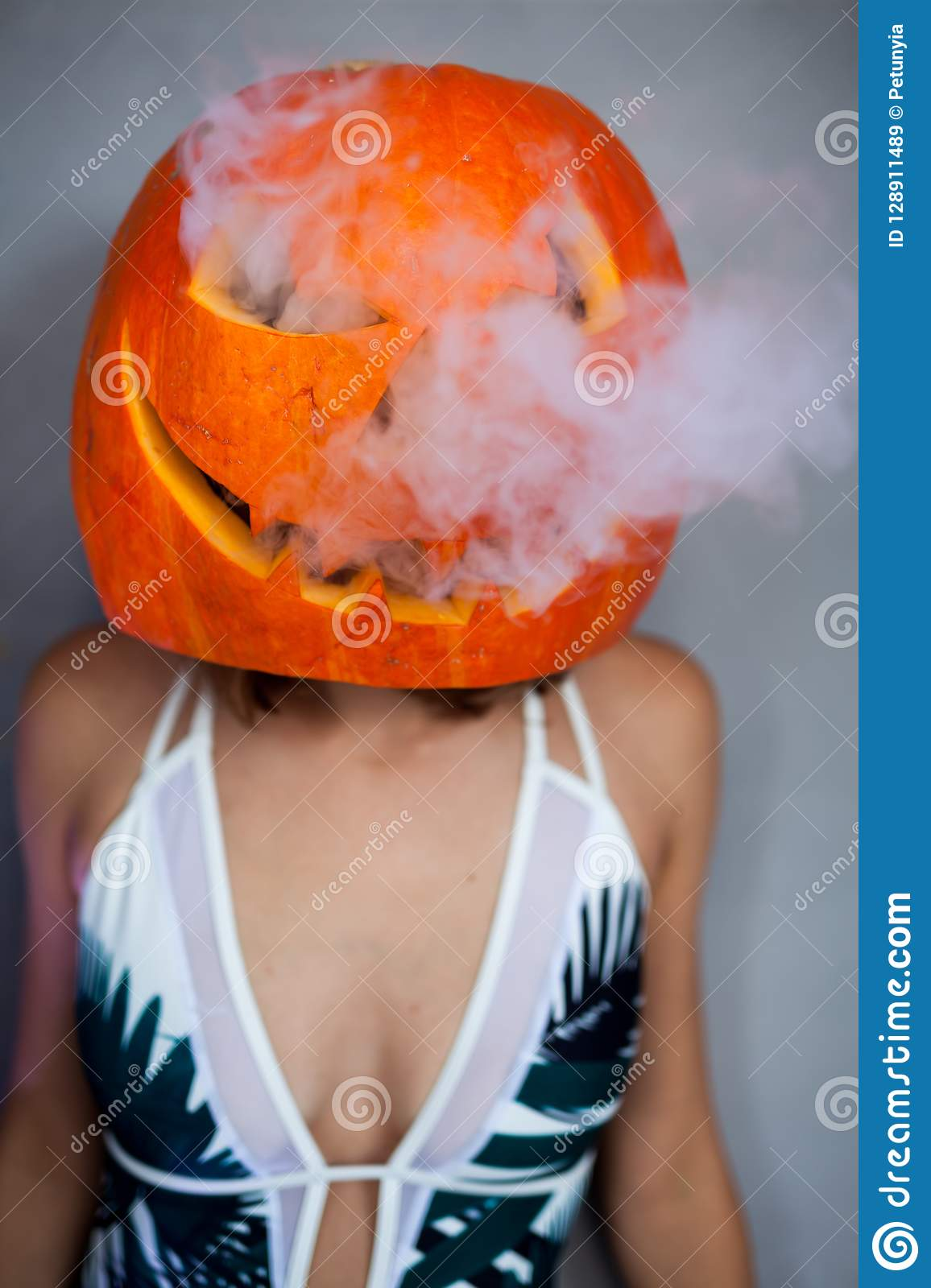 woman with carved pumpkin on her head for Halloween