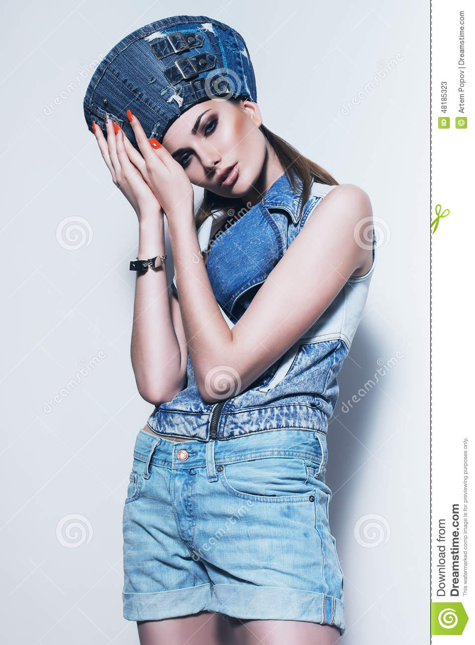 woman in denim hat with orange nails