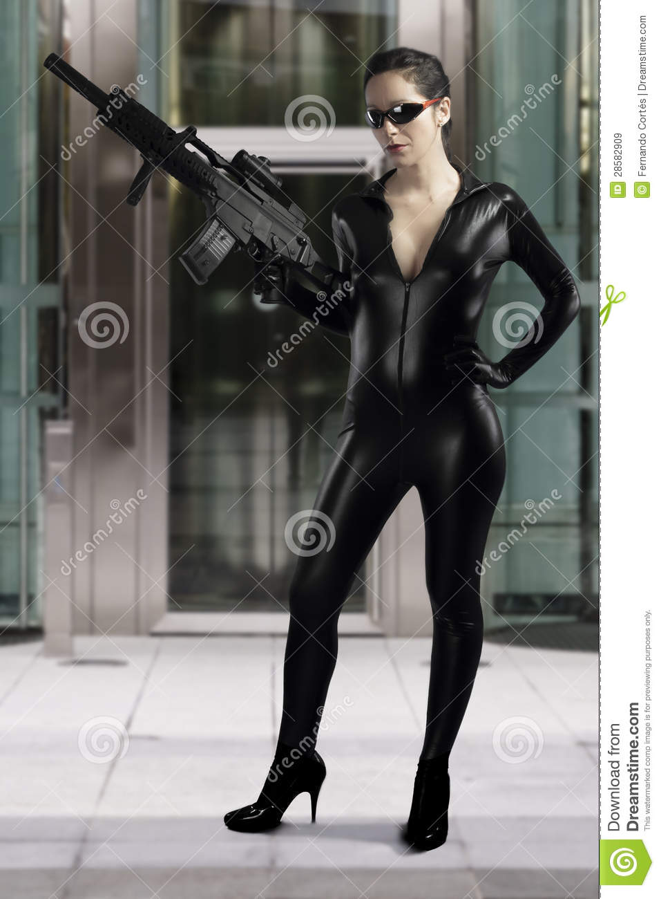 Woman Holding Gun Wearing A Black Leather Dress Stock