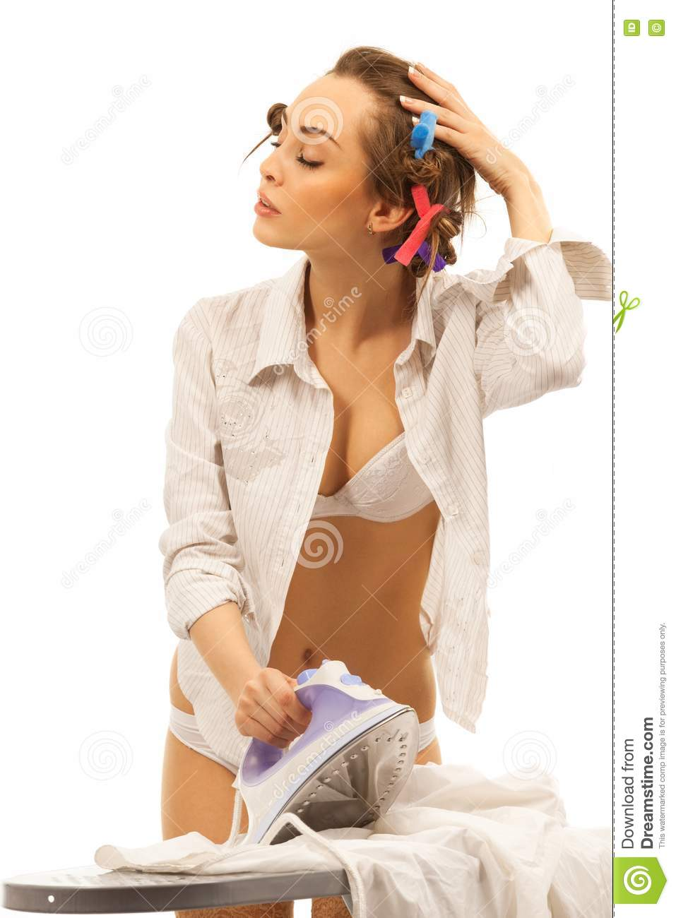Young beautiful sexy woman ironing clothes against bright background