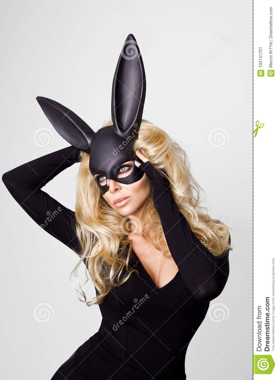 woman with large breasts wearing a black mask Easter bunny standing on a white background