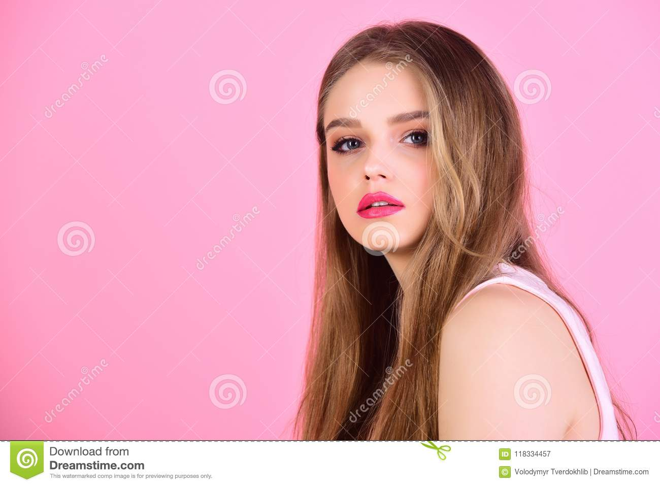 woman with long hair on pink background. Fashion look concept. girl with makeup and healthy hair. Beauty and