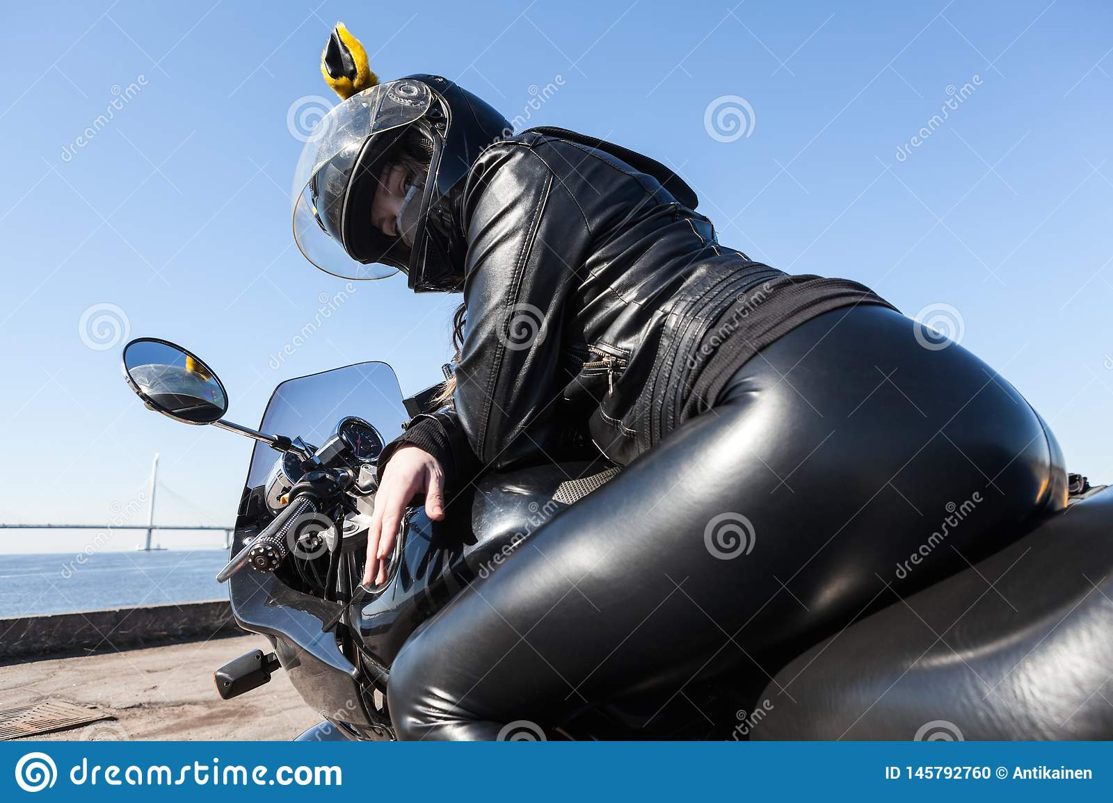 woman motorcyclist in black leather apparel and helmet sitting on bike, rear view, low angle view