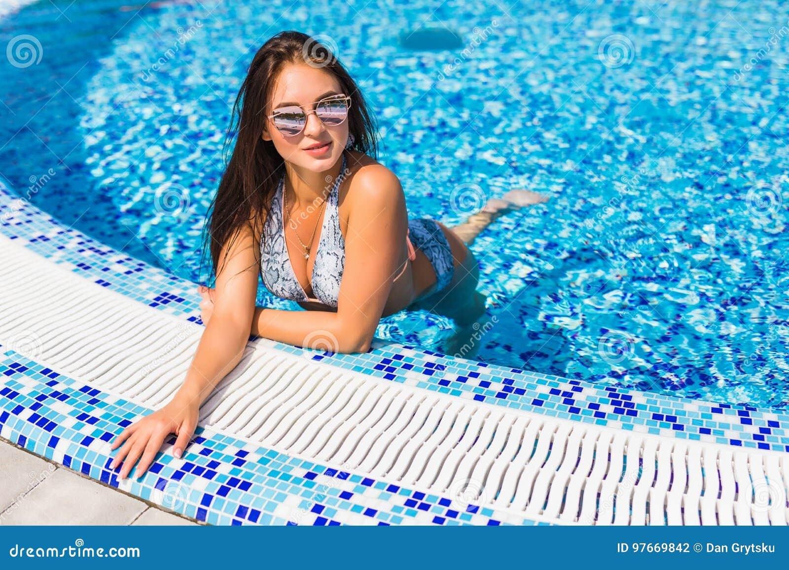 aa08c42c6 woman with perfect curvy body shape in fashionable bikini swimwear relaxing  at swimming pool edge.