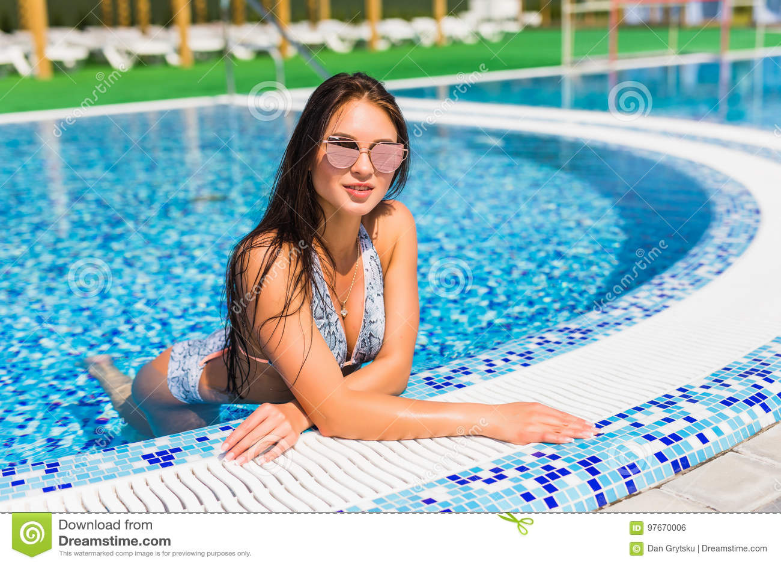 cfbb3d506 woman with perfect curvy body shape in fashionable bikini swimwear relaxing  at swimming pool edge. . Beautiful Girl With Tanned Skin
