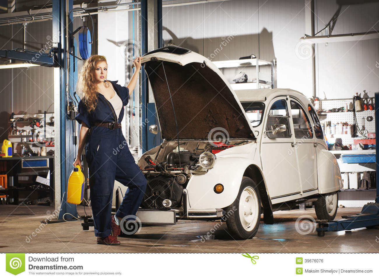 Woman repairing a retro car in a garage stock photo for Garage happy car