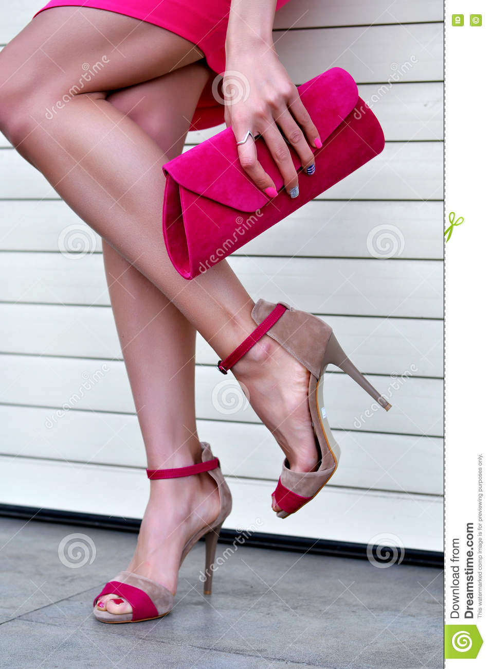 woman's legs with a fashionable pink high heels and purse stock
