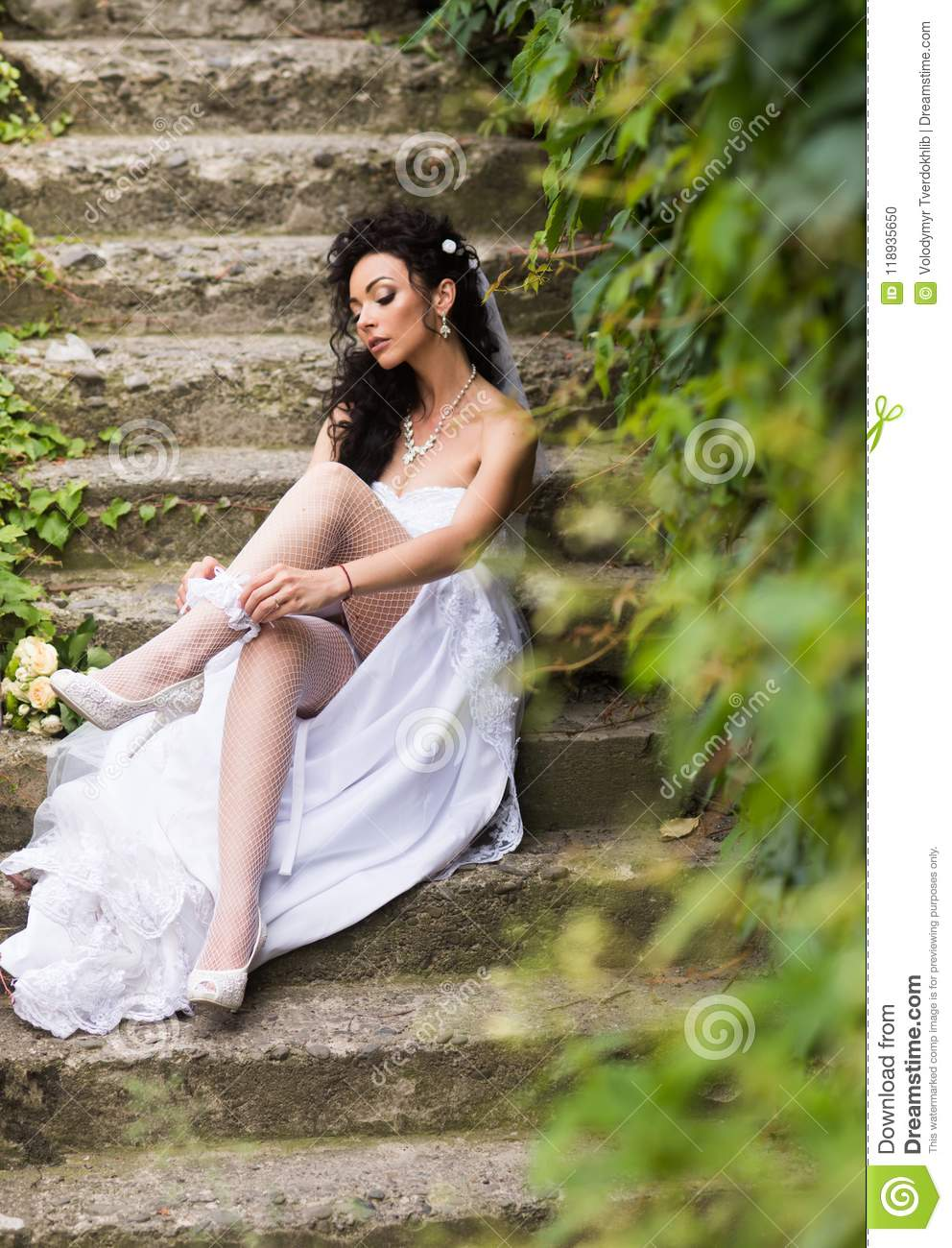 90345f251 Woman wear lace garter on leg. Girl with bridal makeup and hairstyle. Bride  in white dress sit on steps outdoor. Wedding fashion and accessory.