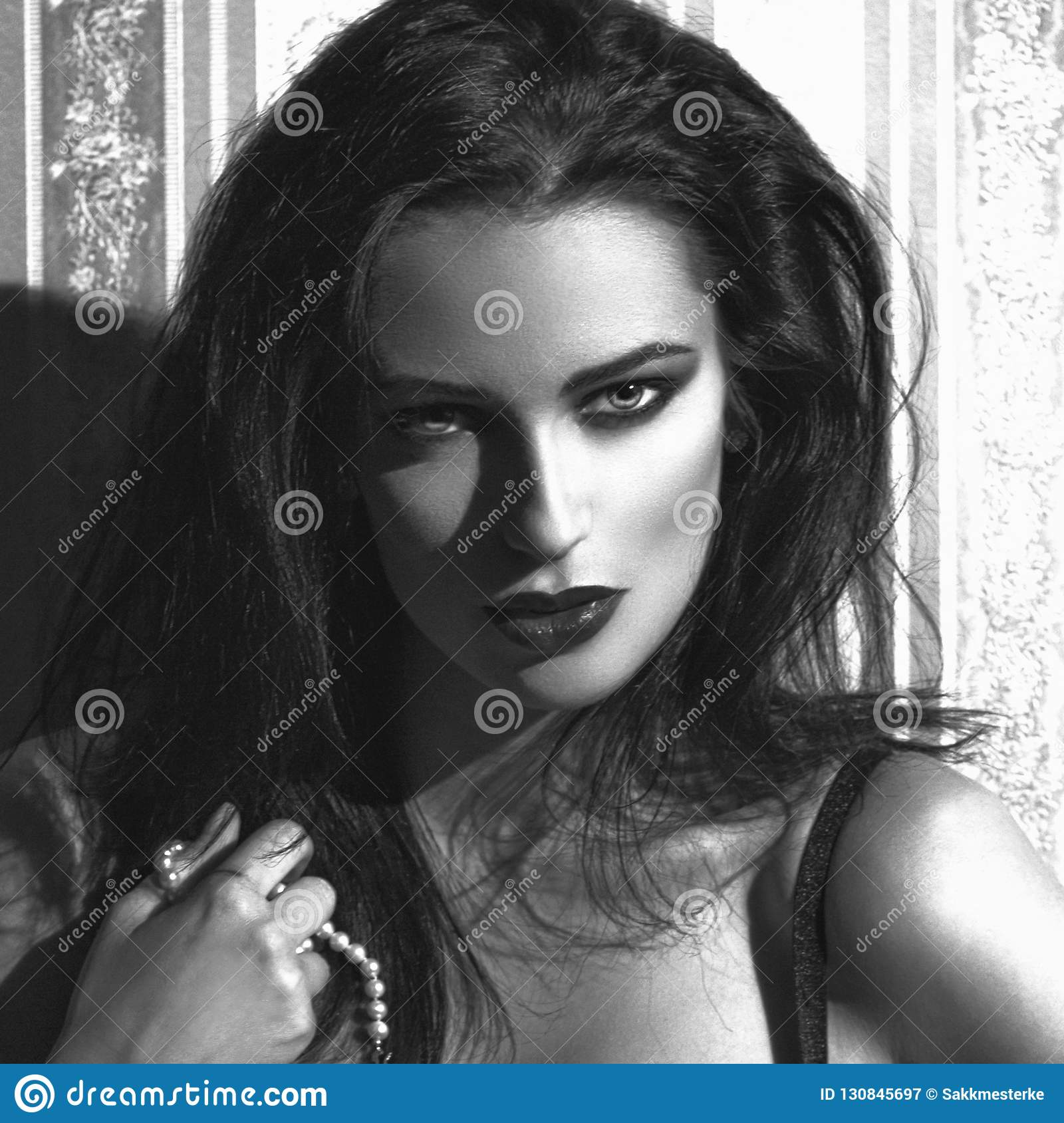 Sensual woman at vintage wall holding pearls portrait black and white