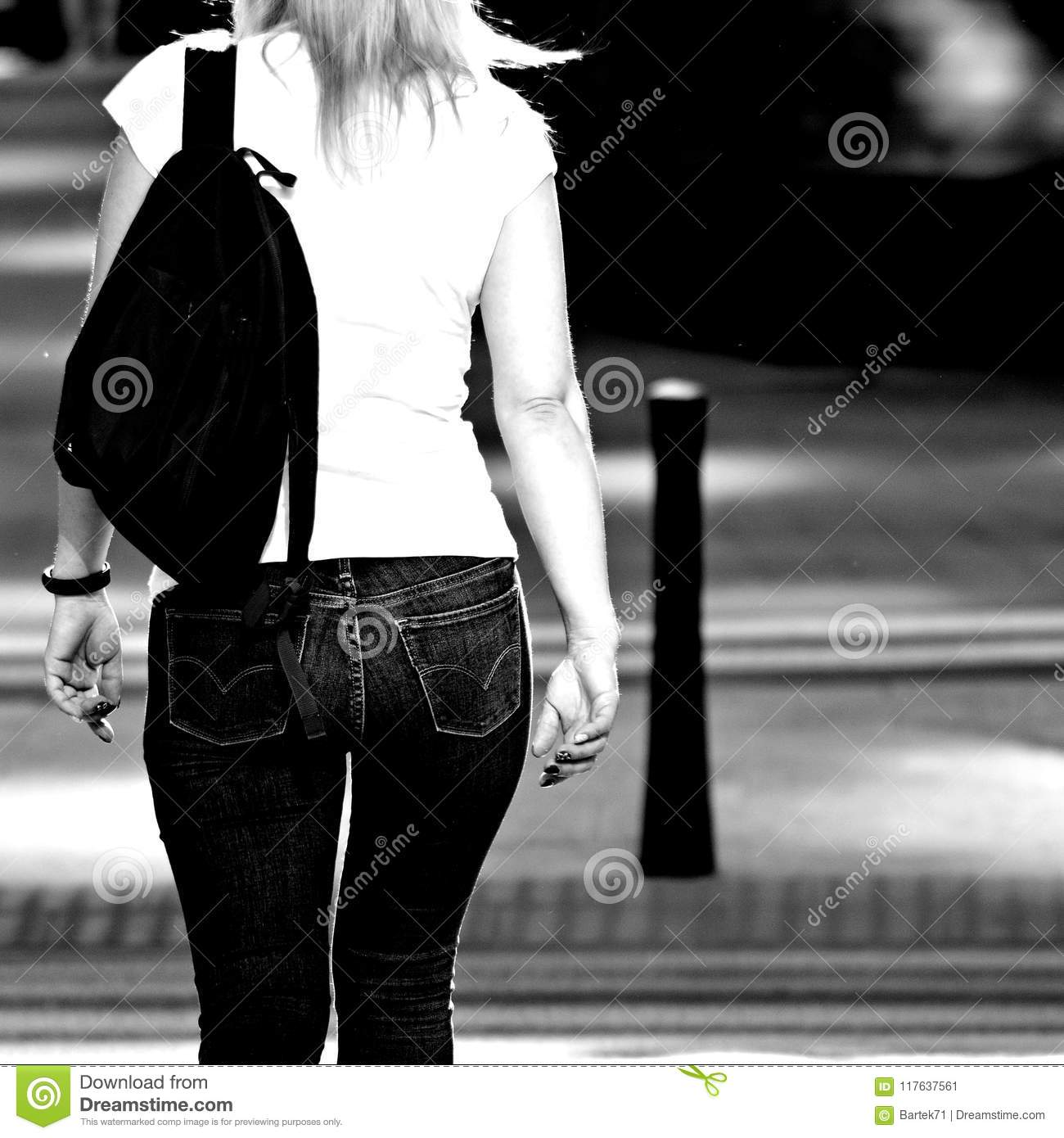 The back view of a girl walking down the street black and white