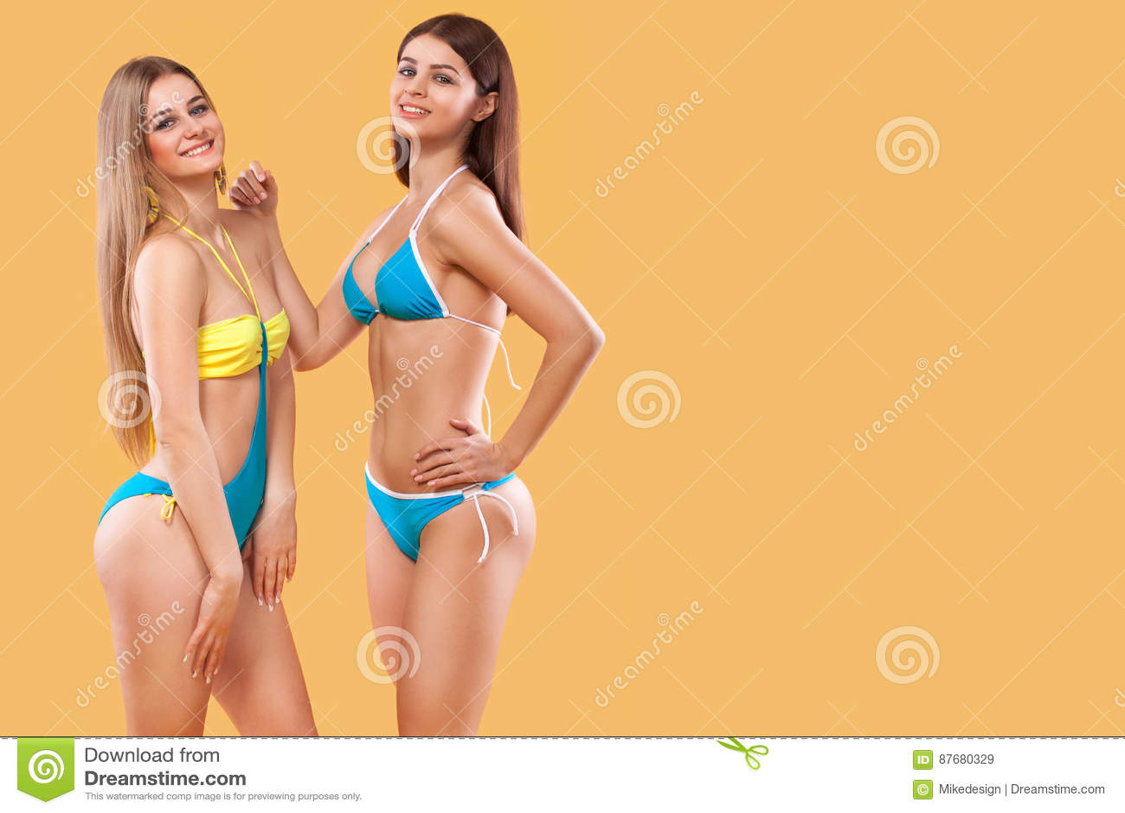 0bfc98a54dd women wearing swimsuit and posing on orange background. Perfect body. Bikini  Summer advertisement concept