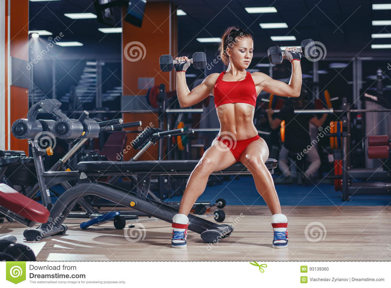 young athletics girl doing dumbbells press exercises sitting on bench in gym