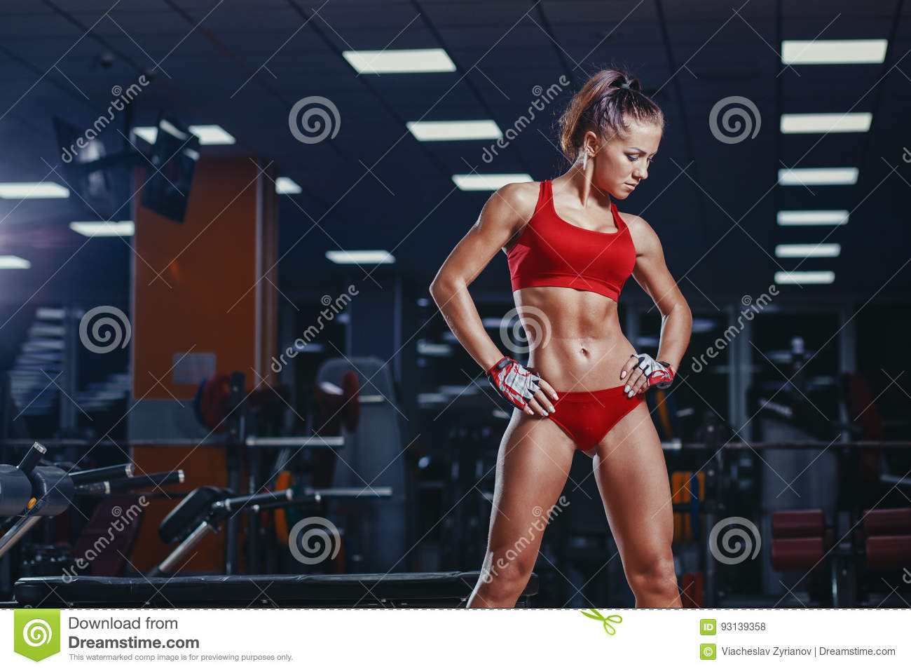 young athletics girl resting after fitness workout in gym.