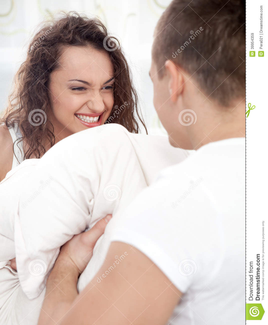 Sexy Young Couple Having Pillow Fight In Bedroom Stock