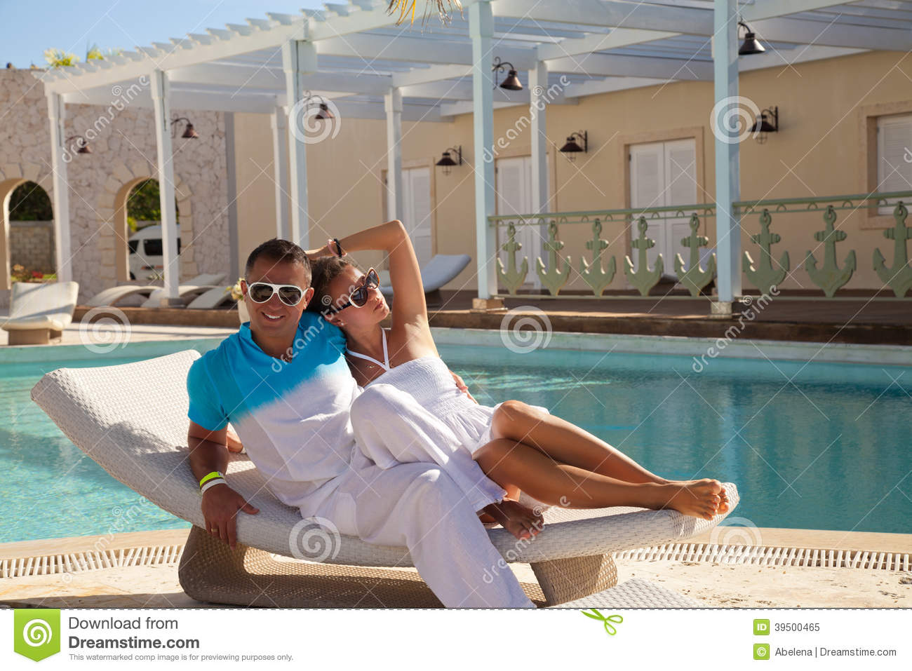 young couple relaxing near pool on a beach bed