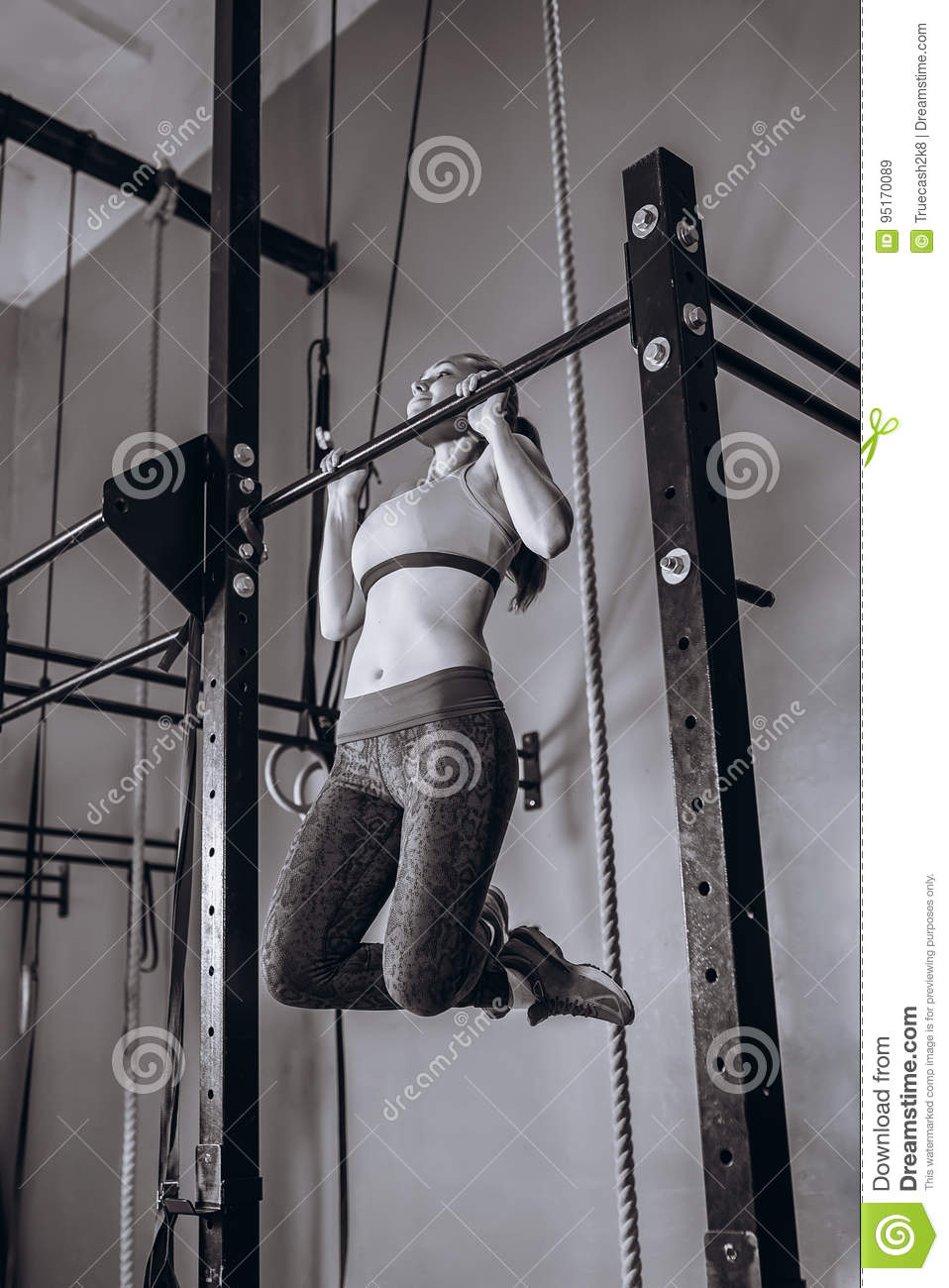 young fit woman doing pull-up on on a crossbeam - horizontal bar. Strong Female fitness at gym.